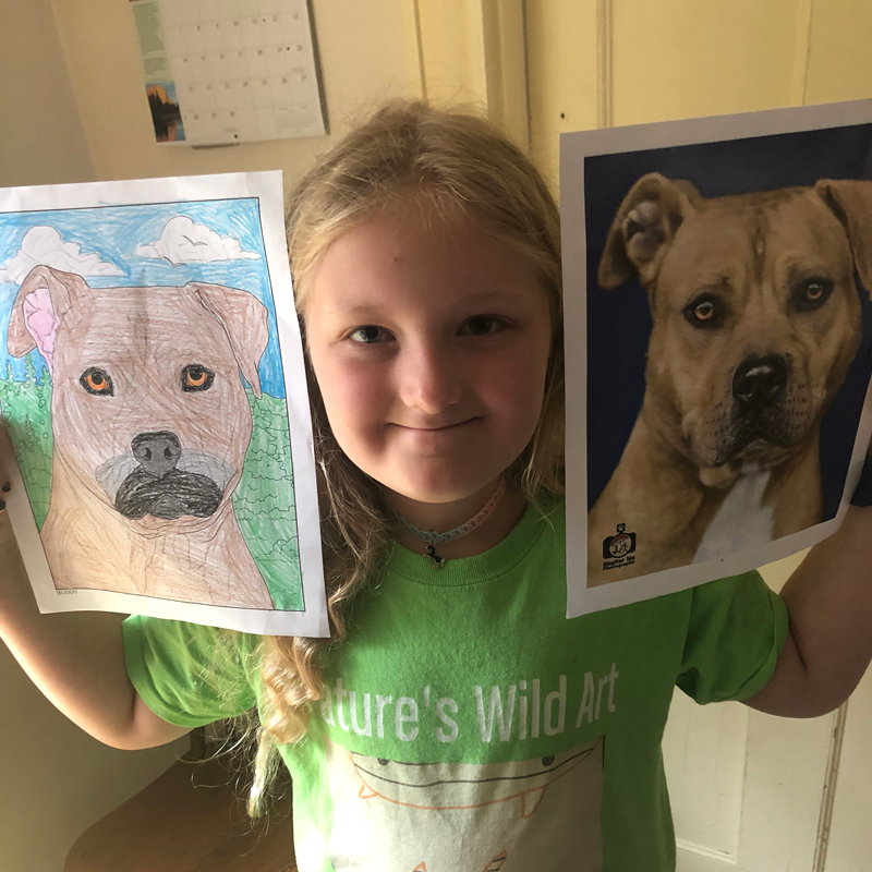 a girl holds her drawing of a dog next to the dog's photo