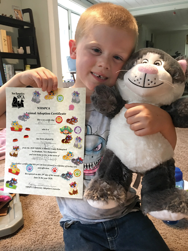 a boy holds up a certificate and a stuffed cat