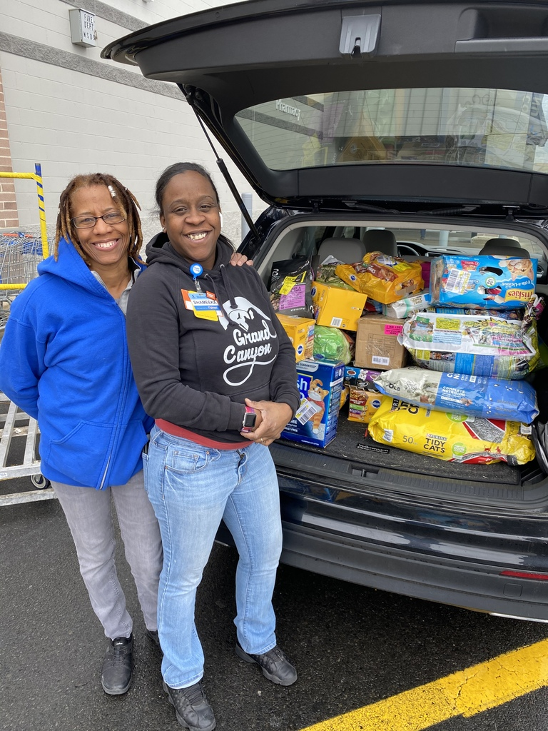 two women pose in front of a car trunk full of pet food and supplies