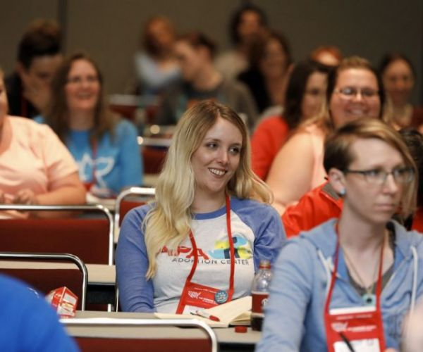 a group of expo attendees smiling during a session