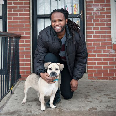 a man poses with his dog on a porch stoop