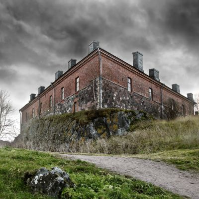a dilapidated building on an overgrown hill with storm clouds overhead