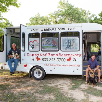 two men and their dogs sit alongside their rescue bus
