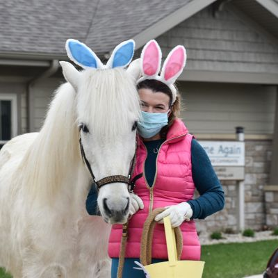 a woman poses next to a white horse, both wearing bunny ears