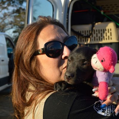 a woman kisses her puppy in front of a transport
