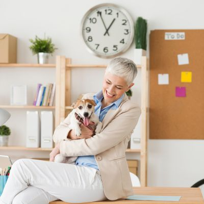 a woman holding a dog in an office setting