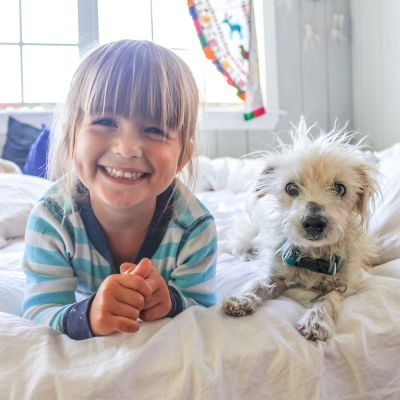 a smiling young girl and dog laying on a bed
