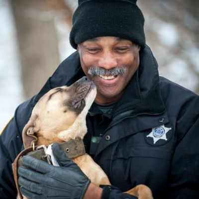 a  dog licks the face of a law enforcement officer