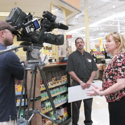 a woman being interviewed in front of a camera in the grocery store