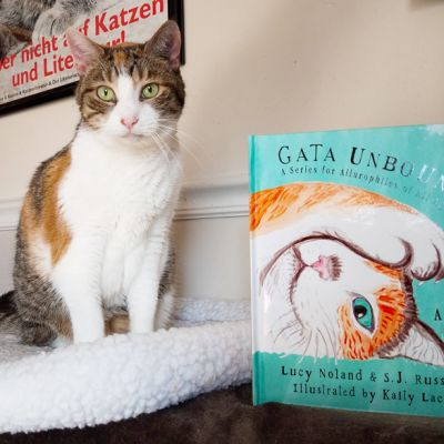 a cat posing alongside the book Gata Unbound