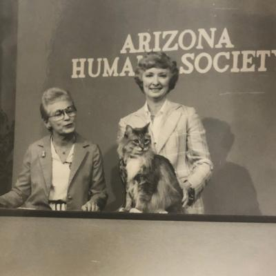black and white photo of two women presenting a cat on tv