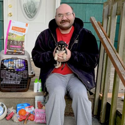 a man holds his puppy while surrounded by pet supplies on his porch