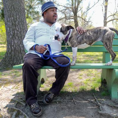 A man sitting on a bench with a dog
