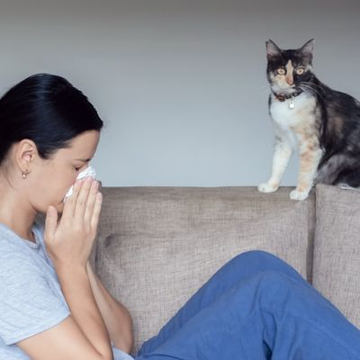 a woman sneezes into a tissue while her cat looks on