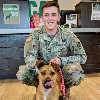 a man in military uniform poses with his shelter dog