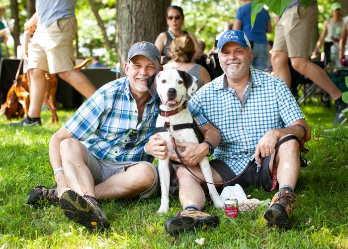 Two men pose with their dog at an outdoor event