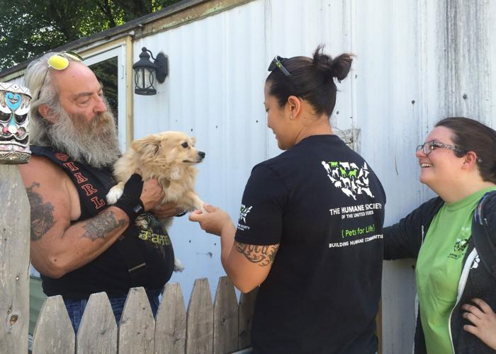 Pets for Life volunteer with dog and owner
