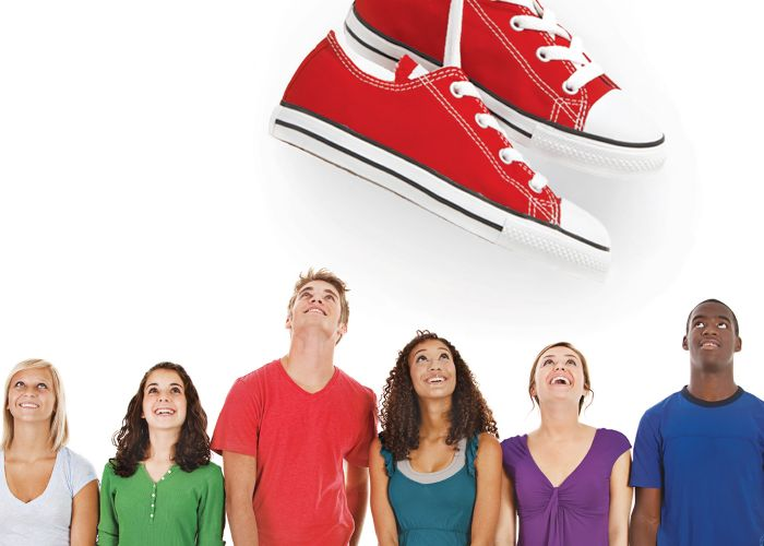 A group of people looking up at a huge pair of shoes