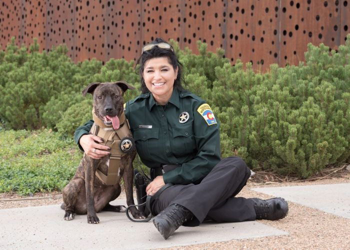 a woman in uniform poses next to a dog in a bullet-proof vest