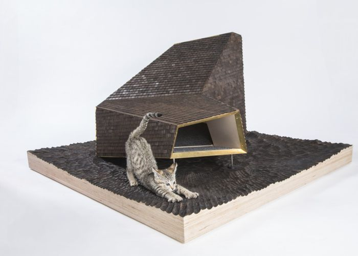 a cat stretching atop an angular enclosure