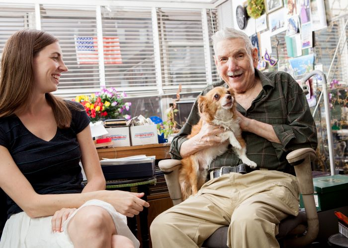 a smiling elderly man holds his dog while a younger woman looks on