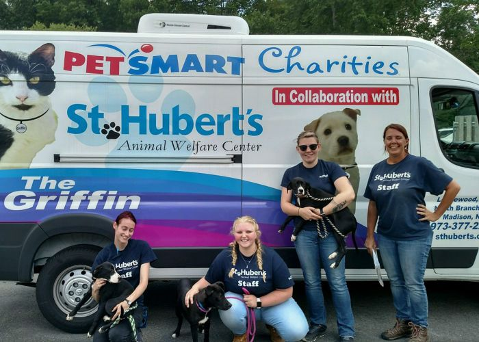four women pose with dogs in front of a van