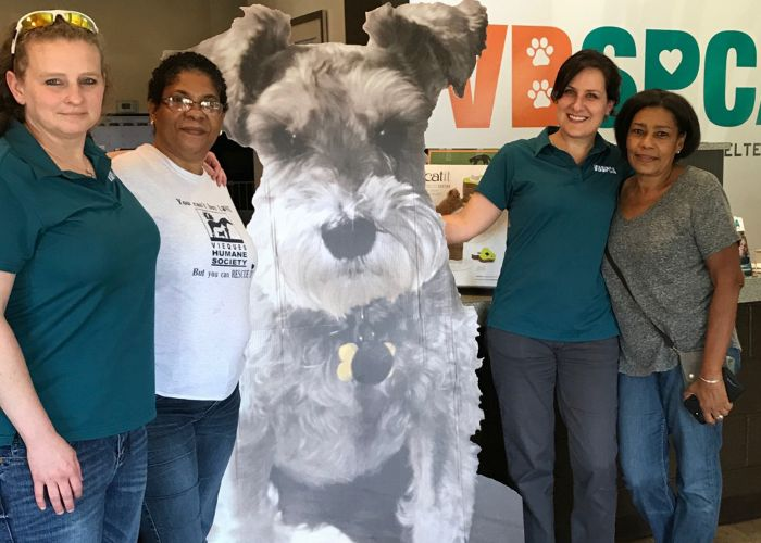 four women gathered around a large cardboard cutout of a dog