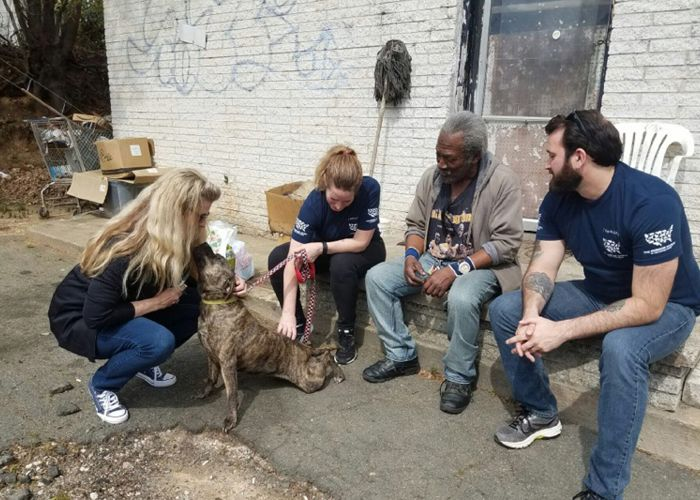 four people gathered around a dog in an impoverished area