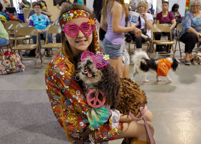 A girl holds a dog, both dressed as hippies