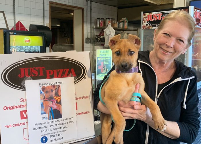 a woman holds a puppy in front of a pizzeria
