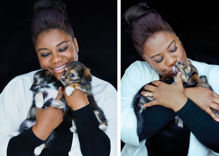 a woman snuggles two small puppies