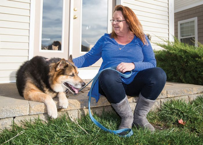 a woman pets her dog while they both sit on a porch