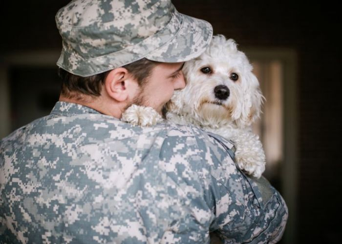 a soldier in camo snuggling a white dog